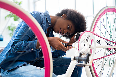 Young woman in casuals repairing bicycle at home - p300m2274781 by Giorgio Fochesato