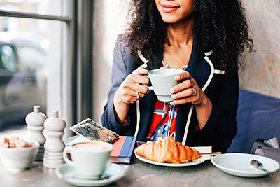 Cropped shot of woman holding coffee cup in cafe - p429m1418073 by Alys Tomlinson