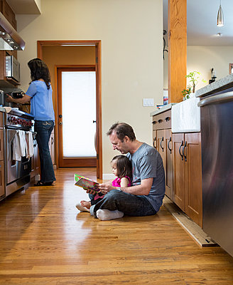 Father reading to daughter in kitchen - p555m1420328 by Sam Diephuis