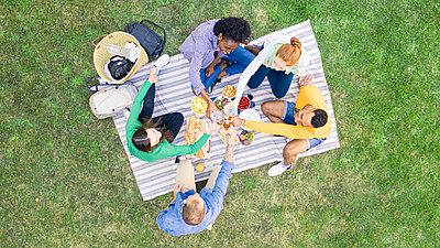 Happy young friends toasting beer bottles in garden - p623m2294746 by Gabriel Sanchez