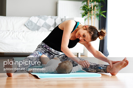 Mother with baby exercising on yoga mat at home - p300m1581495 von gpointstudio