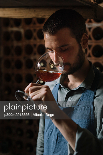 Young man tasting wine from glass in cellar - p300m2213893 by Alberto Bogo