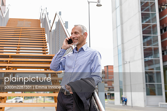 Senior man with shirt leaning against metal staircase railing smiling and talking on mobile phone; Florence, Italy - p300m2287331 von Emma Innocenti