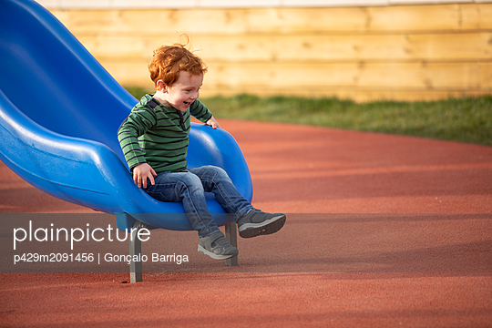 Boy playing on slide in playground - p429m2091456 by Gonçalo Barriga