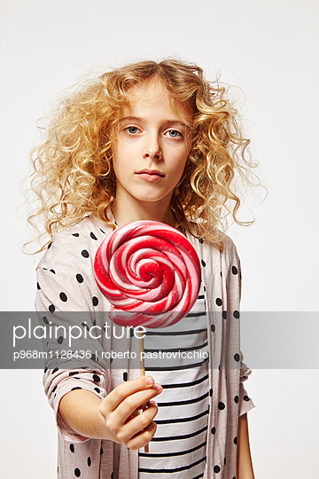 Blonde girl holding red lollipop - p968m1128436 by roberto pastrovicchio