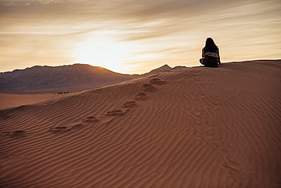 Rear view of woman sitting on sand at desert against cloudy sky during sunset - p1166m1473785 by Cavan Images