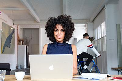 Lächelnde, attraktive Geschäftsfrau mit Afro am Laptop in einem modernen Büro mit jungem Mann auf einem Fahrrad im Hintergrund  - p1301m1589624 von Delia Baum