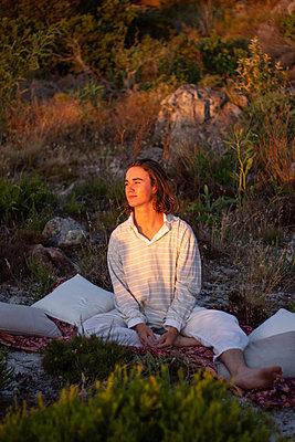 Teenage boy sits on blanket in a meadow - p1640m2242155 by Holly & John
