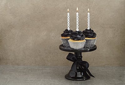 Three cup cakes with black buttercream topping and lighted candles on a cake stand - p300m1120937f by Elisabeth Cölfen