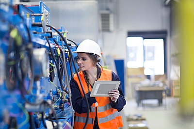 Technician with reflective vest in factory hall inspecting machine with digital tablet - p300m1188324 by Sigrid Gombert