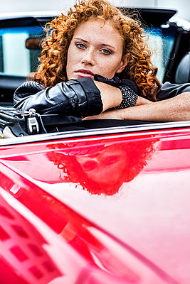 Portrait of confident redheaded woman in sports car - p300m1505405 by Jo Kirchherr