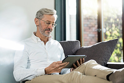 Senior man with grey hair in modern design living room sitting on couch using tablet - p300m2171324 by Steve Brookland
