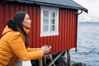 Tourist with cell phone at a hut at the coast, Lofoten, Norway - p300m2180514 by Manu Padilla Photo