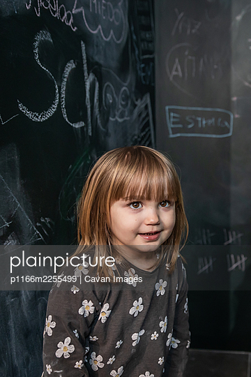 Cute little girl looks on with smiling face with a blackboard on the b - p1166m2255499 by Cavan Images