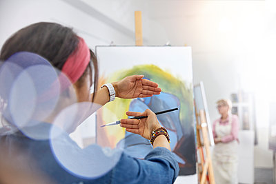 Female artist gesturing, framing painting on easel in art class studio - p1023m1506483 by Rafal Rodzoch