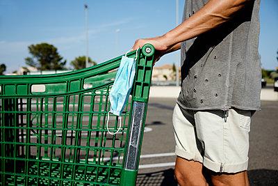Man pushing a shopping cart wearing his face mask in his hand - p1423m2210327 by JUAN MOYANO