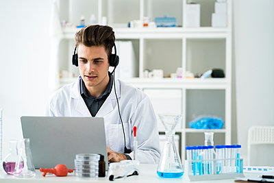 Young male scientist with headphones during video call on laptop in laboratory - p300m2265464 by Giorgio Fochesato