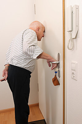 Old man looking through peephole of apartment door - p300m885036f by Albrecht Weißer