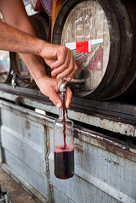 Pouring wine from barrel - p312m1557156 by Lena Granefelt