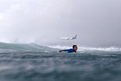Surfer paddling on the sea as a plane flies overhead - p343m1500368 by Konstantin Trubavin