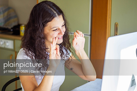 girl speaking sign language on video call - p1166m2213525 by Cavan Images