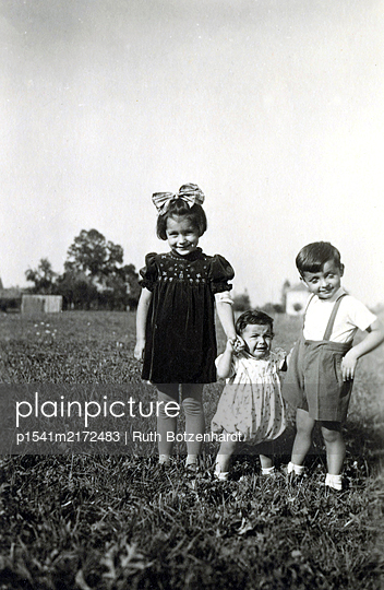 Three children in the meadow in the summertime - p1541m2172483 by Ruth Botzenhardt