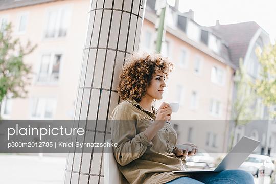 Woman working in a cafe, drinking coffee, using laptop - p300m2012785 von Kniel Synnatzschke