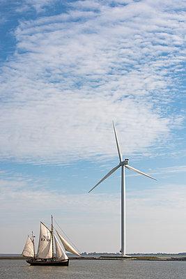 Windrad mit Segelschiff im Vordergrund - p1079m1137133 von Ulrich Mertens