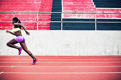 Side view of determined female athlete running on tracks - p1166m1086170f by John Trice