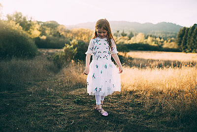 Full length of girl wearing white dress while playing at park - p1166m1530593 by Cavan Images