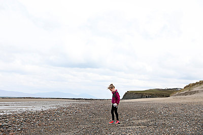 Young Curly Haired Blonde Girl Stands on Rocky Irish Beach - p1166m2094749 by Cavan Images