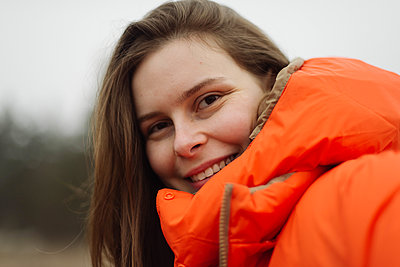 Portrait of young woman smiling outdoors - p1166m2162705 by Cavan Images