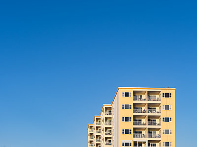 Apartment building against blue sky - p1335m1586373 by Daniel Cullen