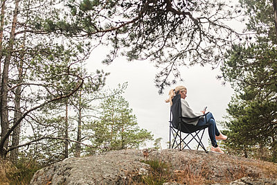 Full length of woman using mobile phone while sitting on camping chair over rock formation against trees - p426m2145646 by Maskot