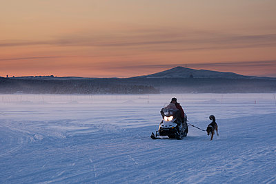 A snow mobile crossing the frozen River Torne at sunset, Jukkasjarvi, Sweden, Scandinavia, Europe - p871m1480341 by Sergio Pitamitz