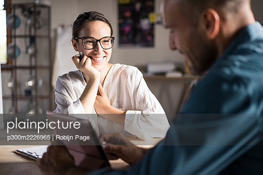 Smiling woman looking at man using digital tablet while sitting at office - p300m2226965 by Robijn Page