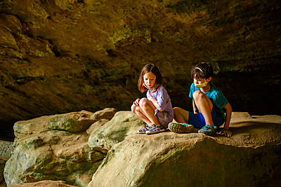 two small serious children sit together on a rocky ledge in gorge - p1166m2218586 by Cavan Images
