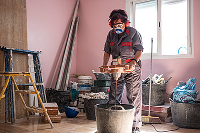 Senior woman using stirrer for mixing paint at construction site - p300m1470005 by Jaen Stock