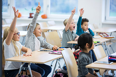 Happy pupils raising their hands in class - p300m2004207 von Fotoagentur WESTEND61