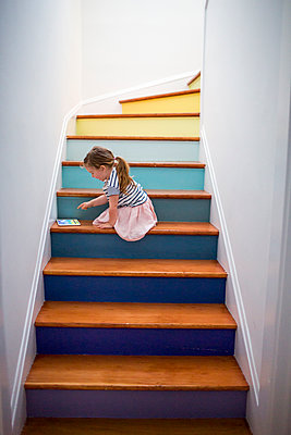 Caucasian girl using digital tablet on multicolor staircase - p555m1504000 by Adam Hester