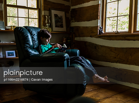 Young boy reading in leather recliner chair in rustic log cabin home. - p1166m2216674 by Cavan Images