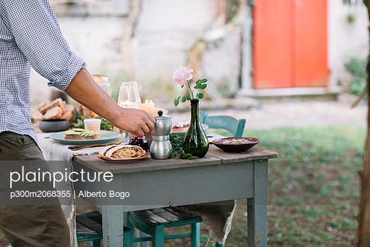 Close-up of man taking moka pot from garden table - p300m2068355 by Alberto Bogo
