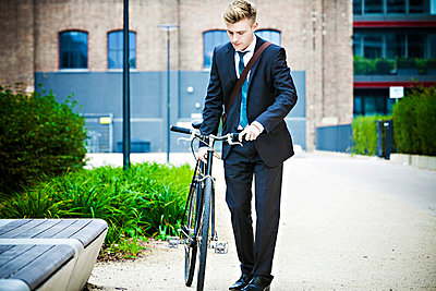 Young businessman with bicycle, Munich, Bavaria, Germany - p1026m991986f by Dario Secen