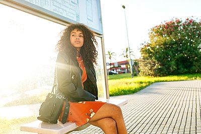 Portrait of young woman waiting at bus stop - p300m2081005 von Kiko Jimenez