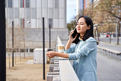 Businesswoman looking away while talking on mobile phone at footpath - p300m2276668 by Veam