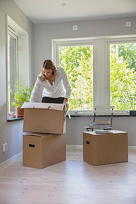 Woman unpacking cardboard box - p352m2119095 by Helena Bonnevier