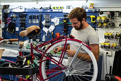 Mechanic repairing bicycle in workshop - p623m2214732 by Frederic Cirou