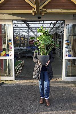 Woman bought a plant at a garden shop.  - p896m1490472 by Richard Brocken