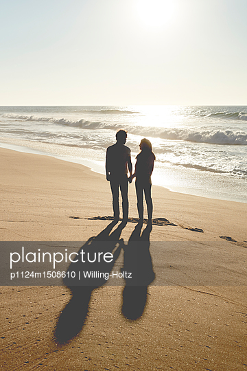 Couple standing on beach - p1124m1508610 by Willing-Holtz