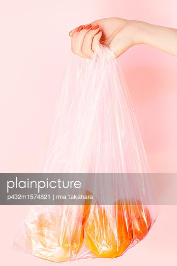 Junge Frau hält Plastiktüte mit Orangen - p432m1574821 von mia takahara